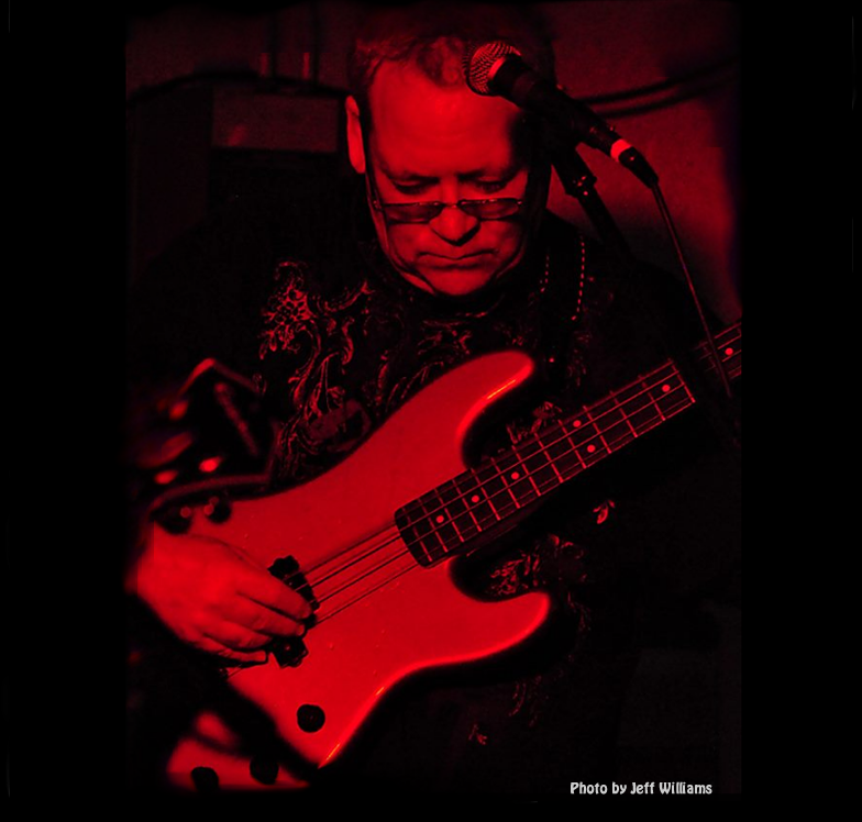 red and black color image of mike capps playing a fender pj bass